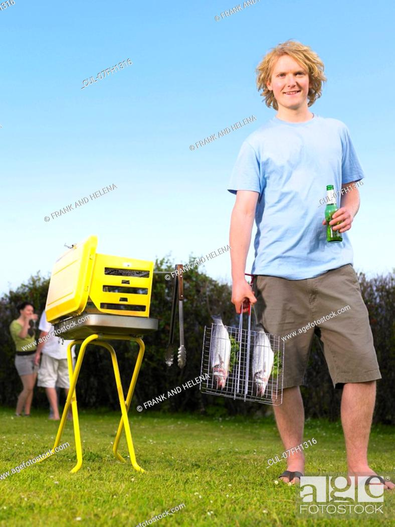 Stock Photo: Young man holding fish next to barbecue.
