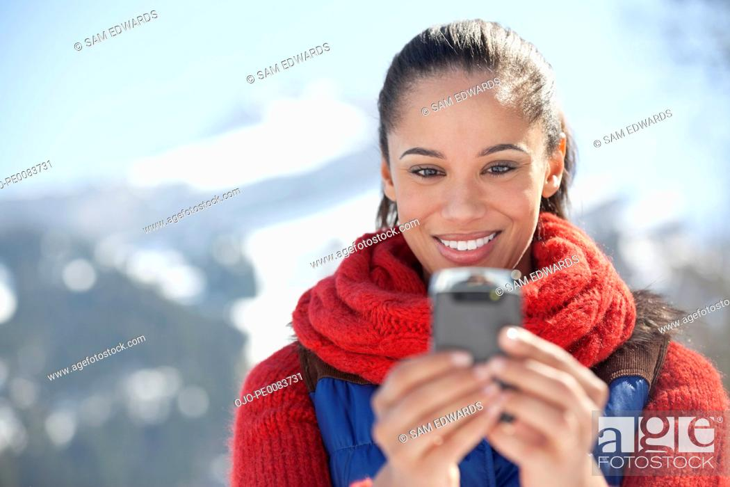 Stock Photo: Smiling woman checking cell phone.