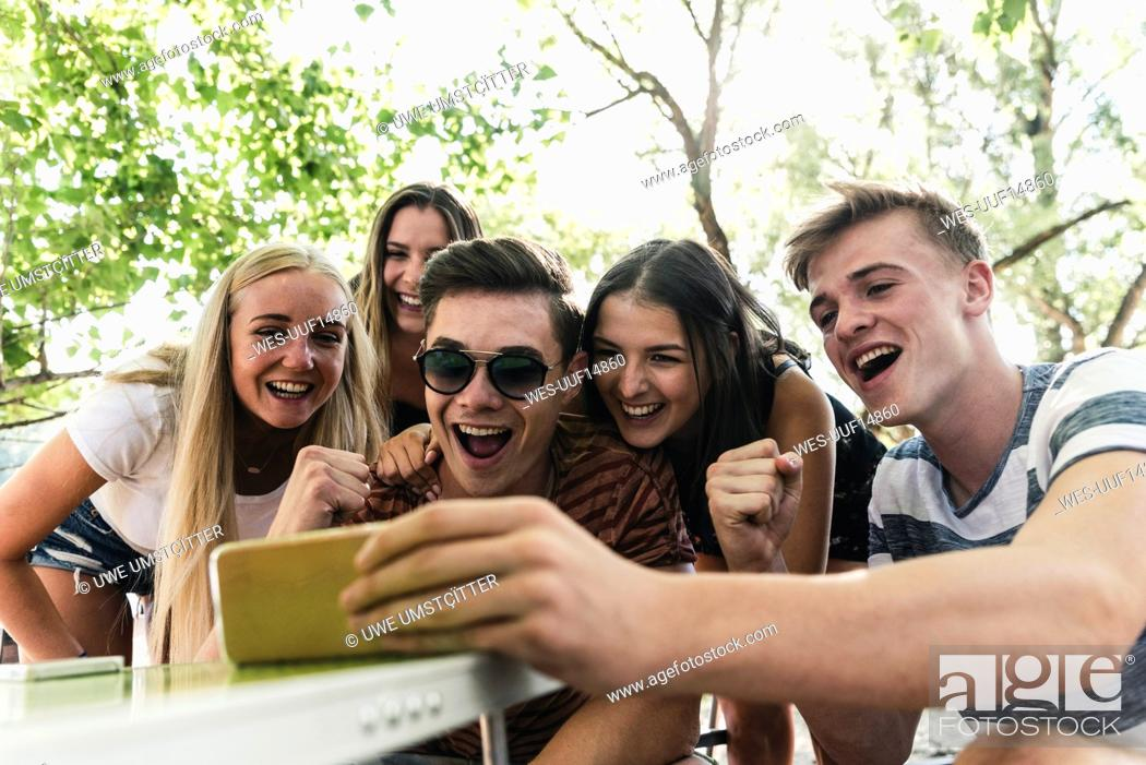 Stock Photo: Group of happy friends looking at cell phone outdoors.