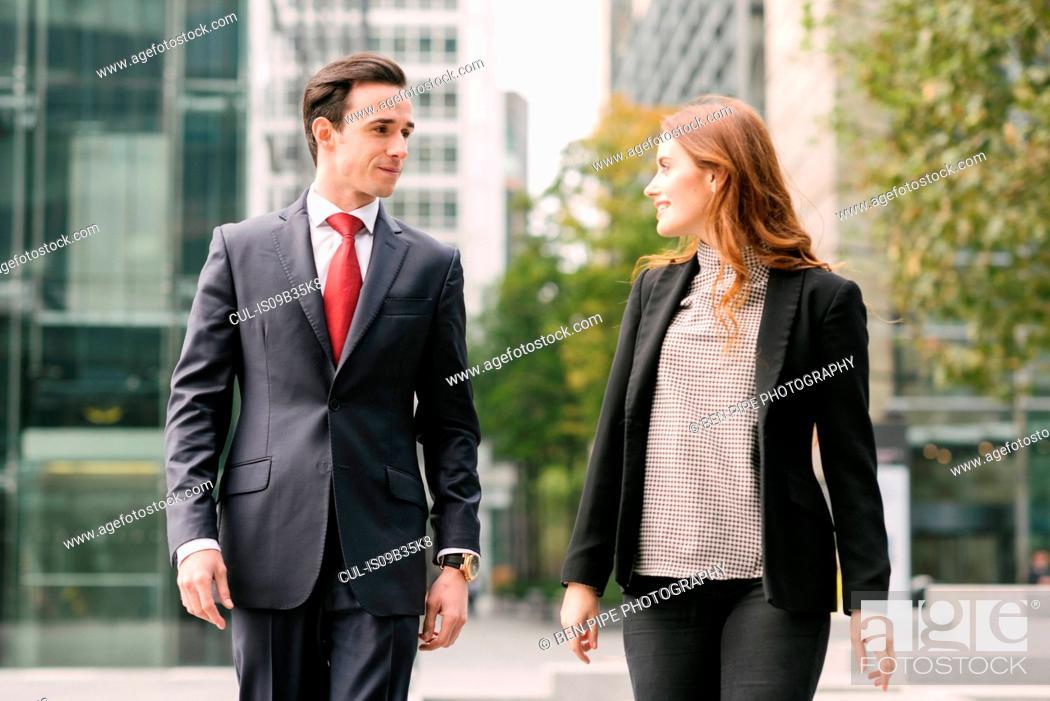 Stock Photo: Business people walking in city talking.