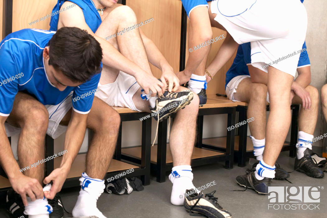 Stock Photo: Footballers putting on boots.