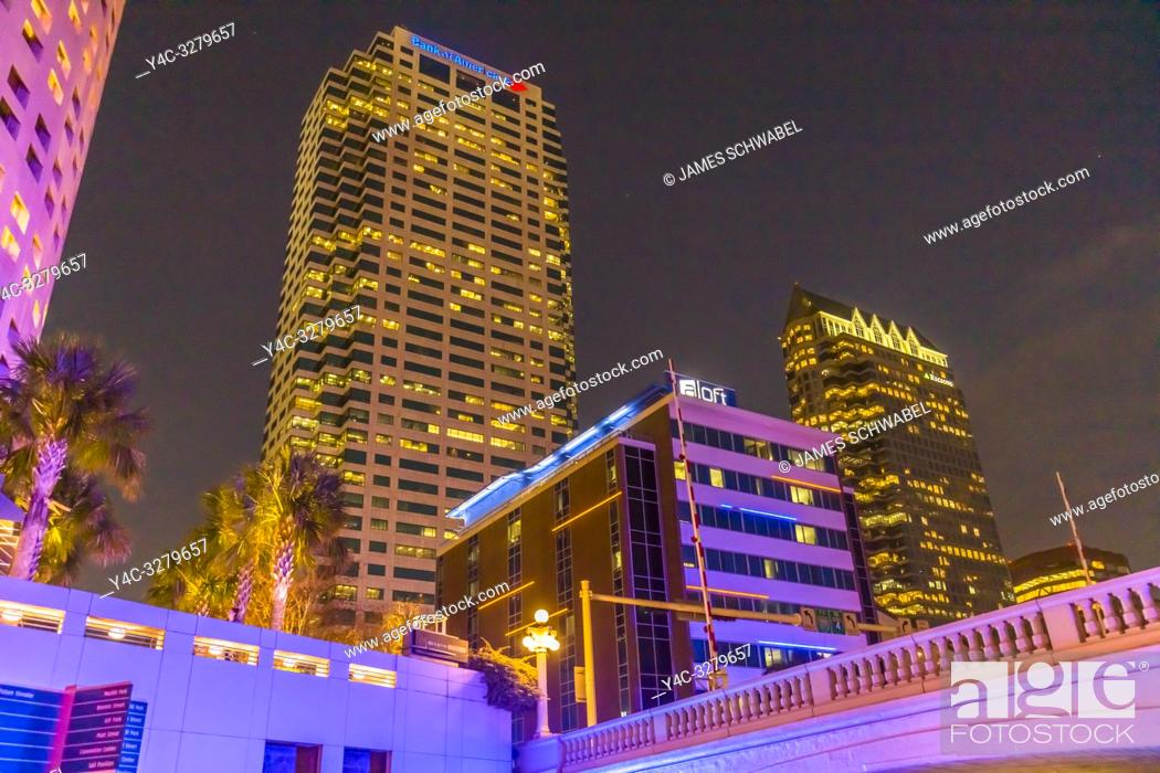 Imagen: Downtown Tampa Florida buildings lit up at night with colorful lights as seen from the Tampa Riverwalk.