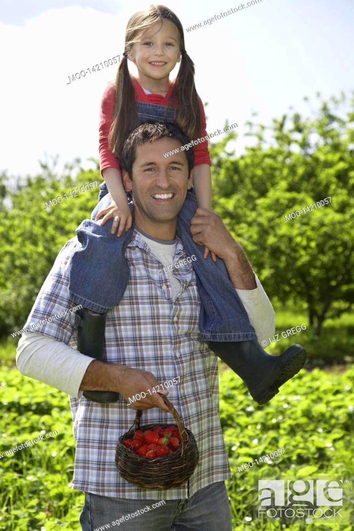 Stock Photo: Girl 5-6 on father's shoulders in strawberry field portrait.