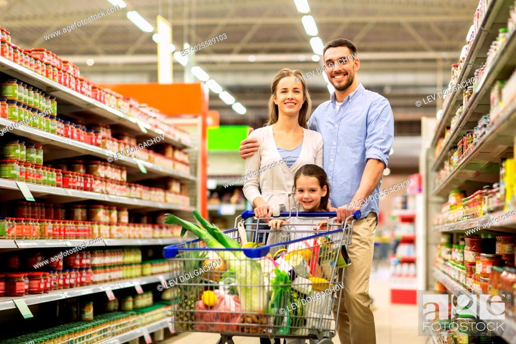 Stock Photo: sale, consumerism and people concept - happy family with child and shopping cart buying food at grocery store or supermarket.