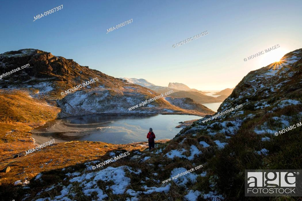 Stock Photo: Hiker looks over the snow-covered mountains and frozen lakes of Lofoten, Lofoten, Nordland, Norway.