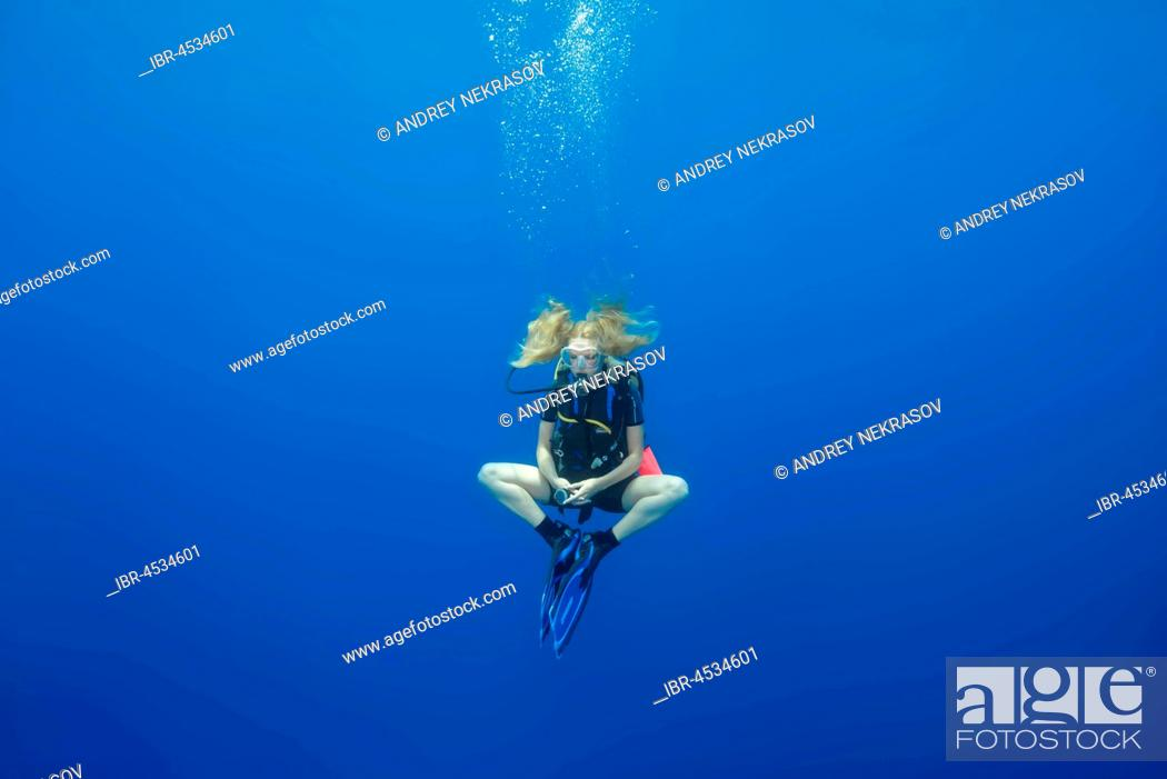 Stock Photo: Female scuba diver hung in a lotus pose for a safety stop, in blue water, Indian Ocean, Maldives.