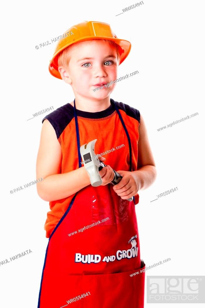 Imagen: Little Caucasian boy dressed in orange with construction helmet and apron with pockets, holding a hammer, isolated.