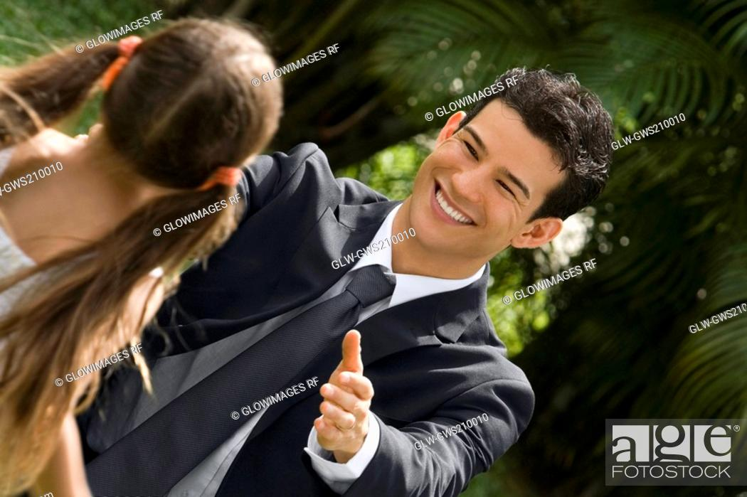 Stock Photo: Young man greeting his daughter and smiling.