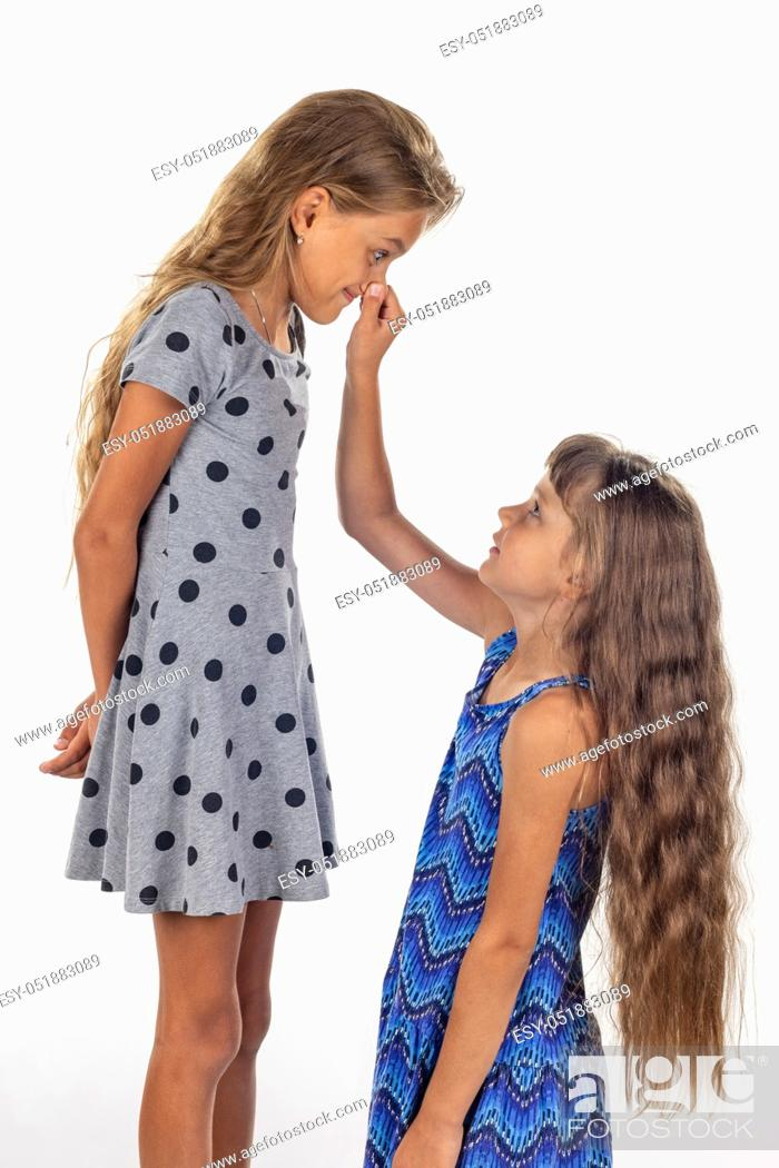 Stock Photo: Two girls, one stood on a chair and the other holds the first by the nose.