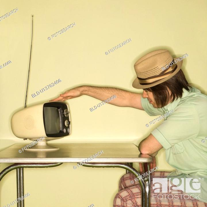 Stock Photo: Man wearing hat sitting at 50's retro dinette set tapping old television set.