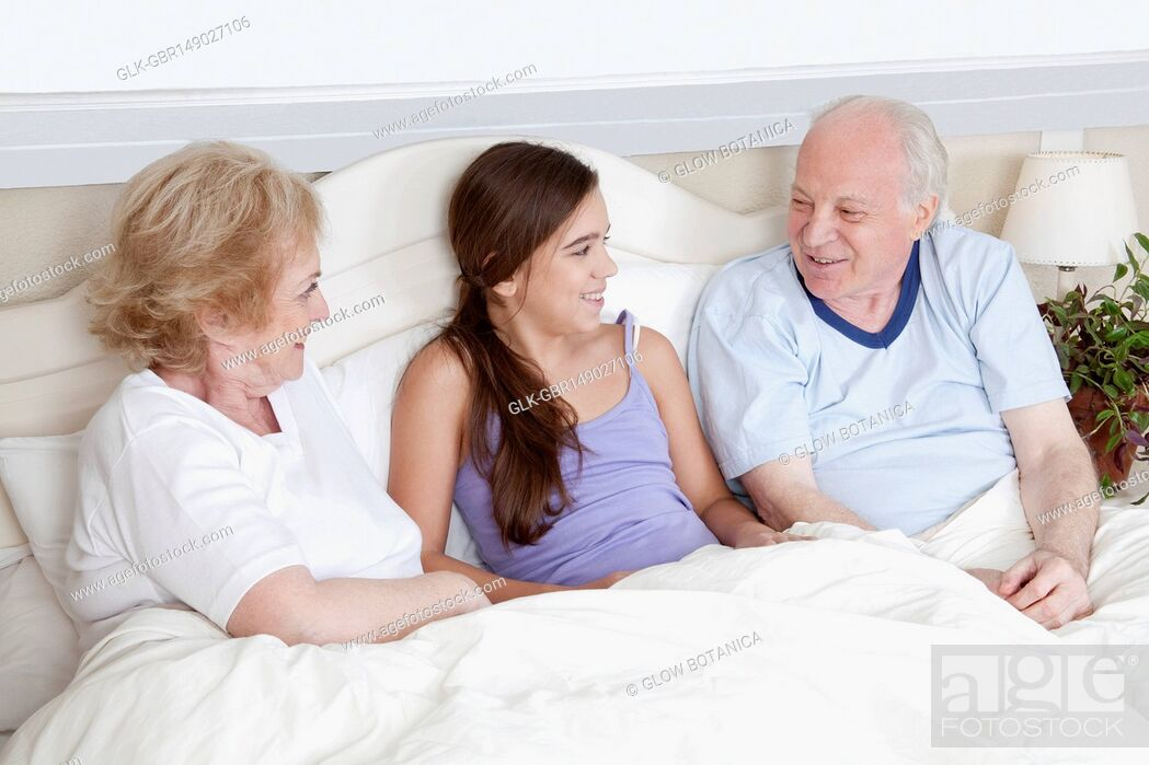 Stock Photo: Family lying in the bed and smiling.
