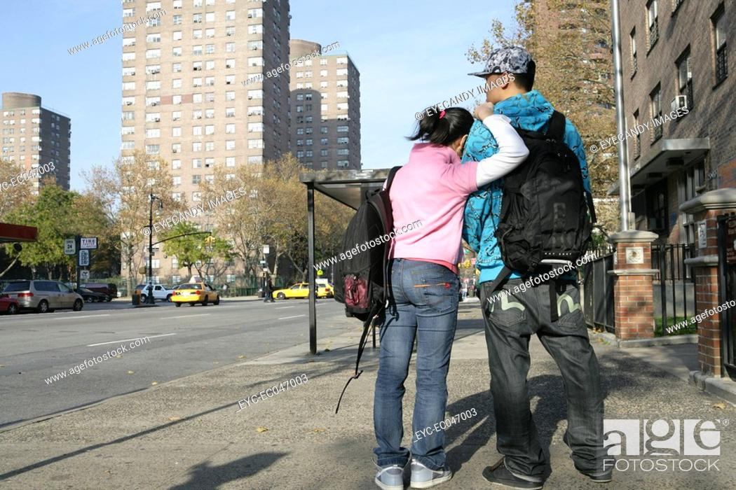 Stock Photo: Teenagers 15-17 standing on pavement, rear view.