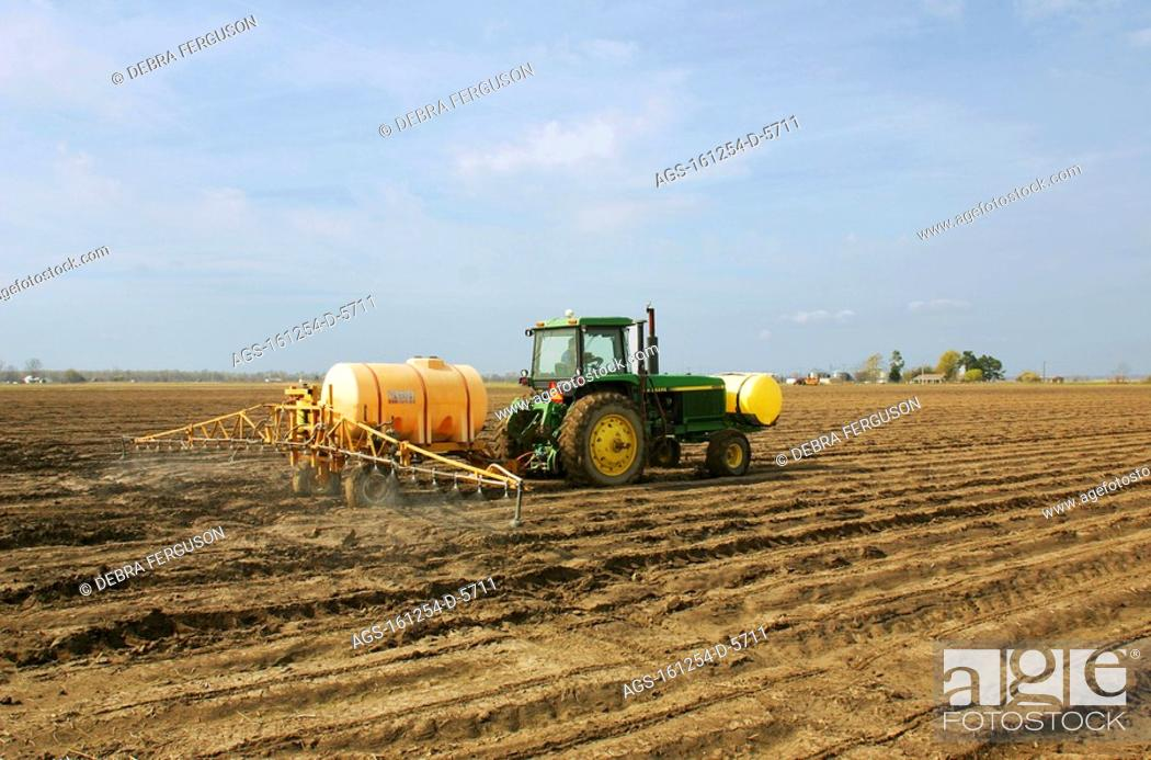 Agriculture - A tractor equipped with a sprayer applies a
