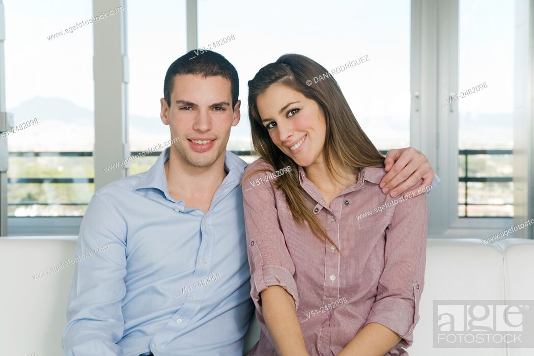 Imagen: Portrait of a beautiful couple in sofa smiling at camera.