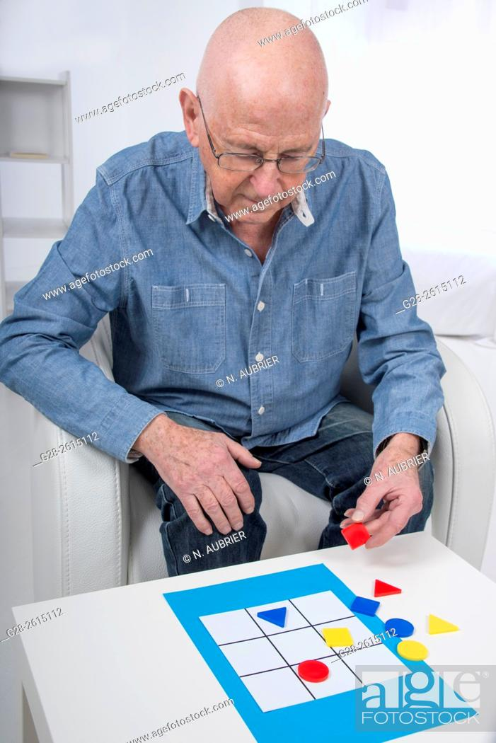 Stock Photo: Senior man playing with a psychological test game to detect Alzheimer disease at home.