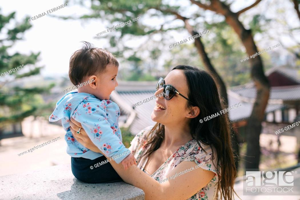 Stock Photo: South Korea, Seoul, Mother and baby girl visiting Changdeokgung Palace and Huwon.