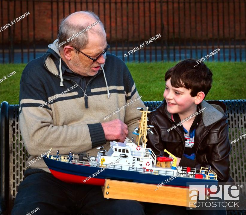 Stock Photo: Young boy and old man discussing model boats in a park.