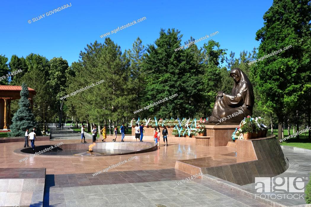 Stock Photo: Tashkent, Uzbekistan - May 12, 2017: Children visiting Crying Mother monument and eternal flame at Independence square.