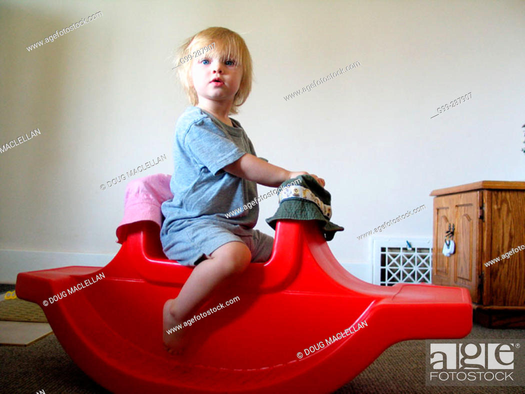 Stock Photo: 18 month old toddler playing on red rocking horse in her home.