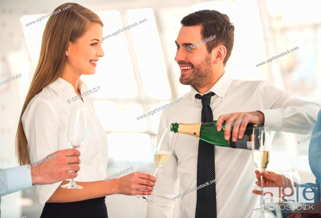 Imagen: Successful business people are drinking champagne, talking and smiling while celebrating in office.