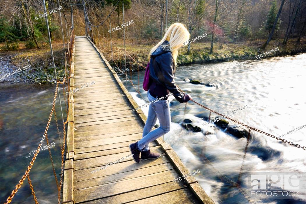 Stock Photo: Attractive young woman on a hanging footbridge.