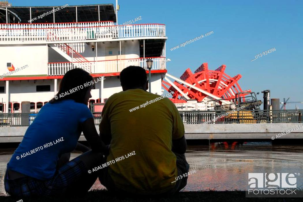 Stock Photo: Couple observing the Natchez steamboat on the Mississippi riverside, New Orleans, Louisiana, United States.