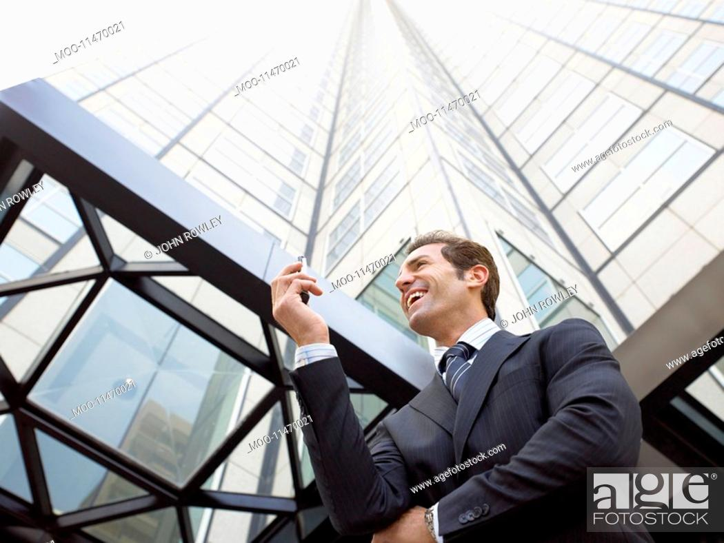 Stock Photo: Businessman reading message on phone outside office low angle view.