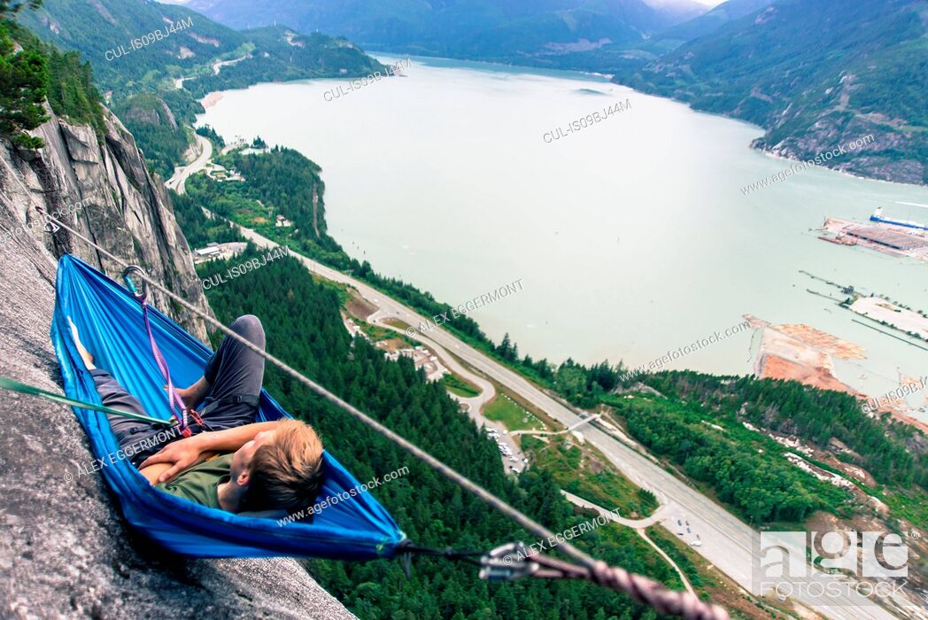 Stock Photo: Young male climber reclining in hammock on bellygood ledge, The Chief, Squamish, Canada.