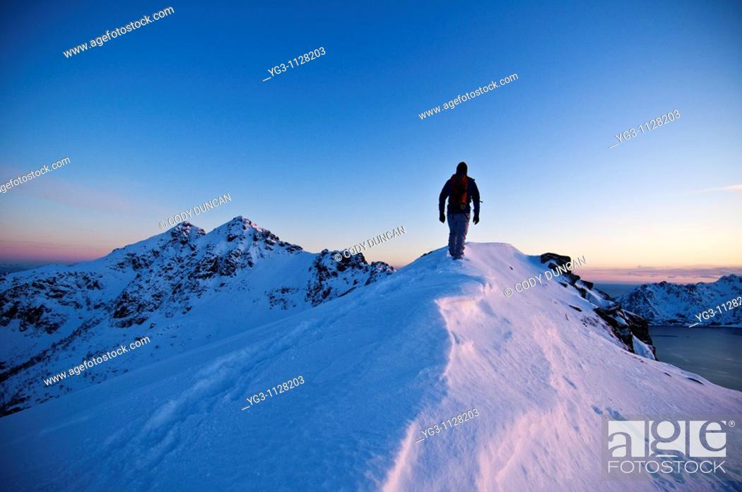 Stock Photo: Person hikes along snow covered ridge of Stamsundheia with Steinstind peak in distance, Stamsund, Vestvågøy, Lofoten islands, Norway.