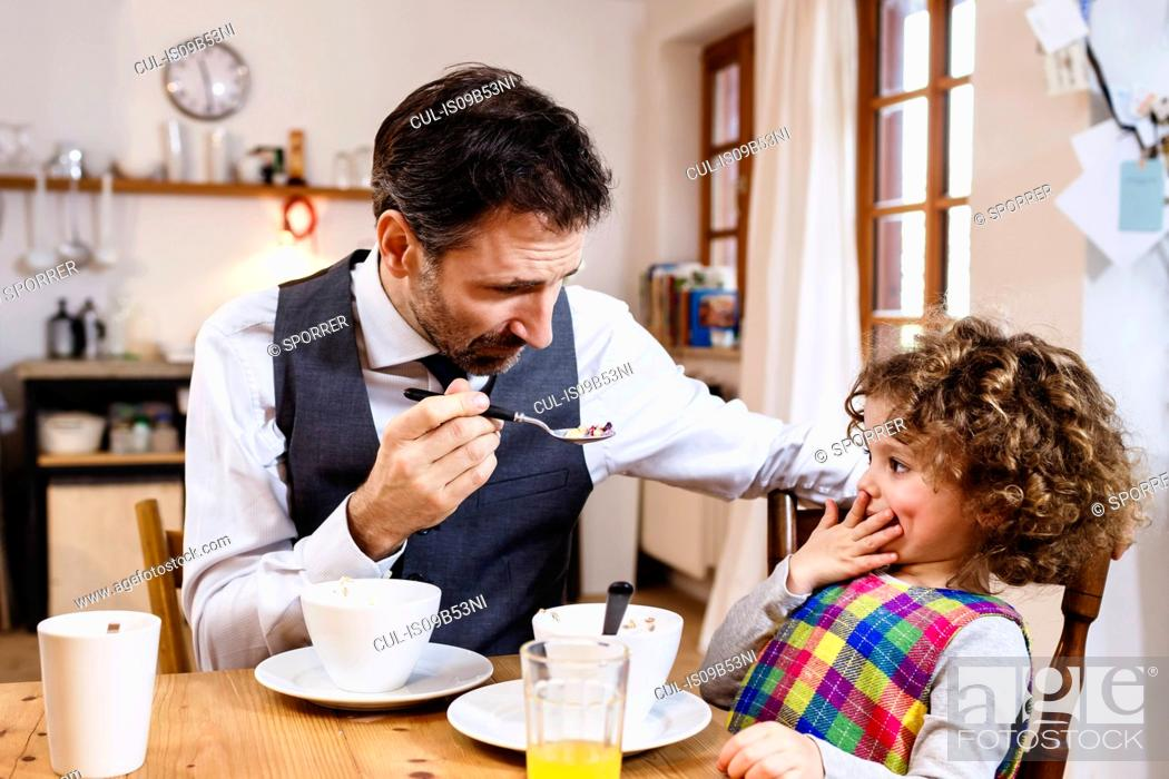 Stock Photo: Man feeding daughter cereal with hand over mouth in kitchen.