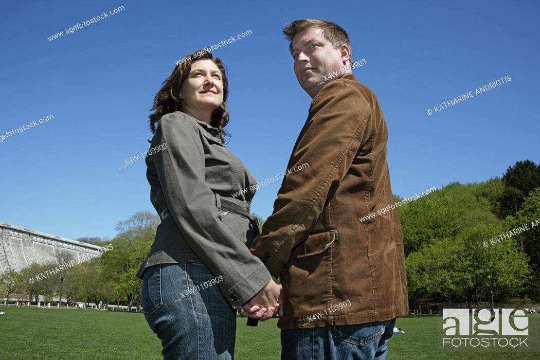 Stock Photo: Couple holding hands on a sunny day in a park.