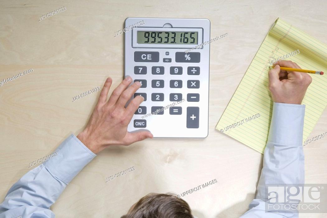 Stock Photo: Businessman using calculator.