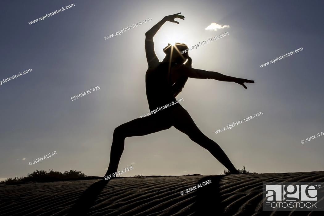 Stock Photo: Side view of female silhouette in beautiful yoga pose standing on beach with sun back lit.