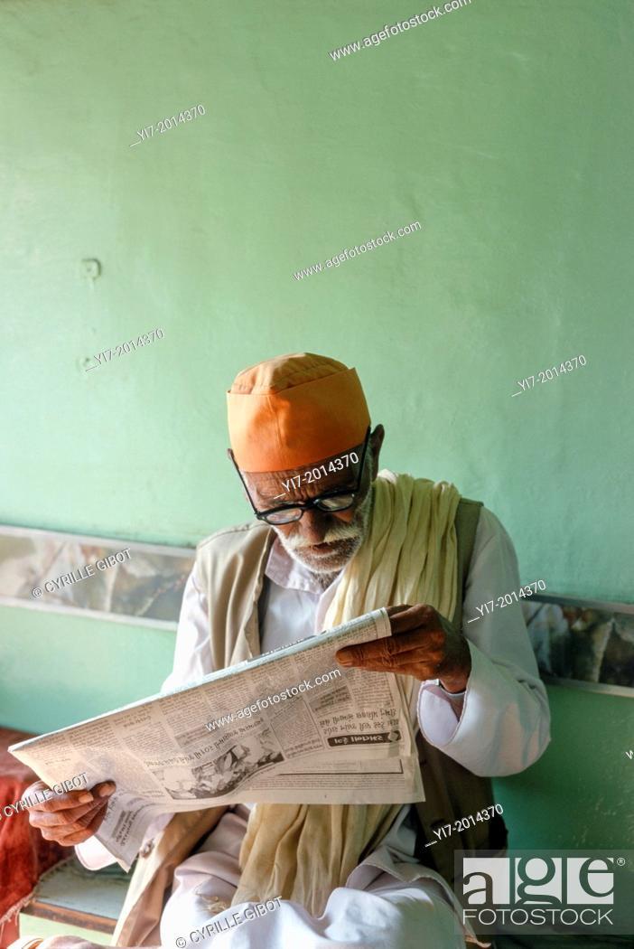Stock Photo: Senior man reading newspaper in cafe, Mandvi, Gujarat, India.