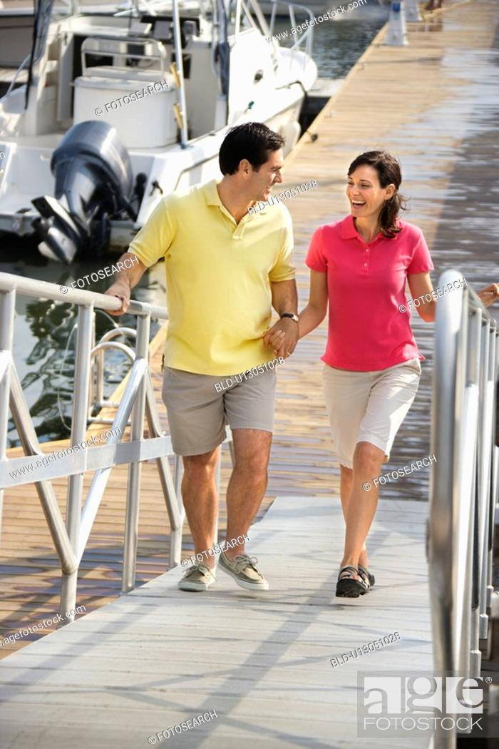 Stock Photo: Mid-adult couple holding hands and walking up ramp at harbor.