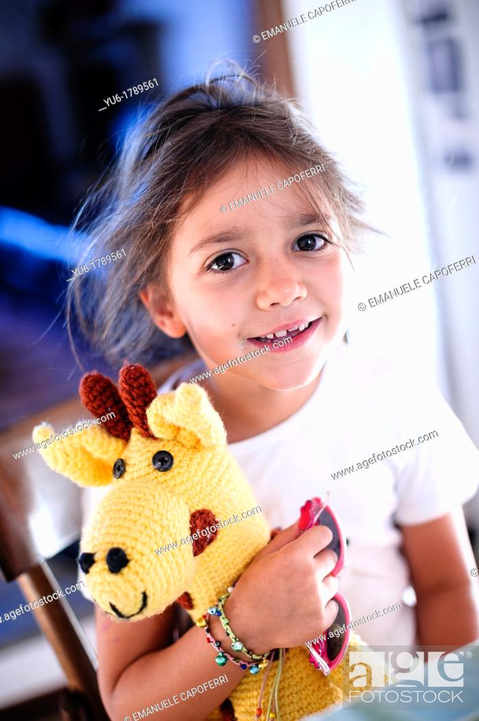 Stock Photo: Little girl with her toy giraffe in the morning sitting at the kitchen table.