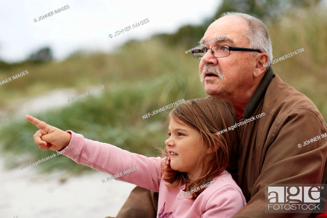 Photo de stock: Grandfather sitting with granddaughter on beach.