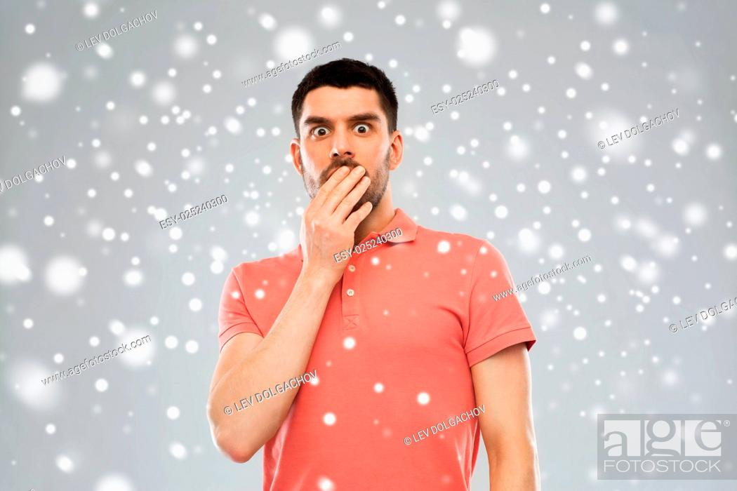 Stock Photo: emotion, fear, winter, christmas and people concept - scared man in polo t-shirt over snow on gray background.