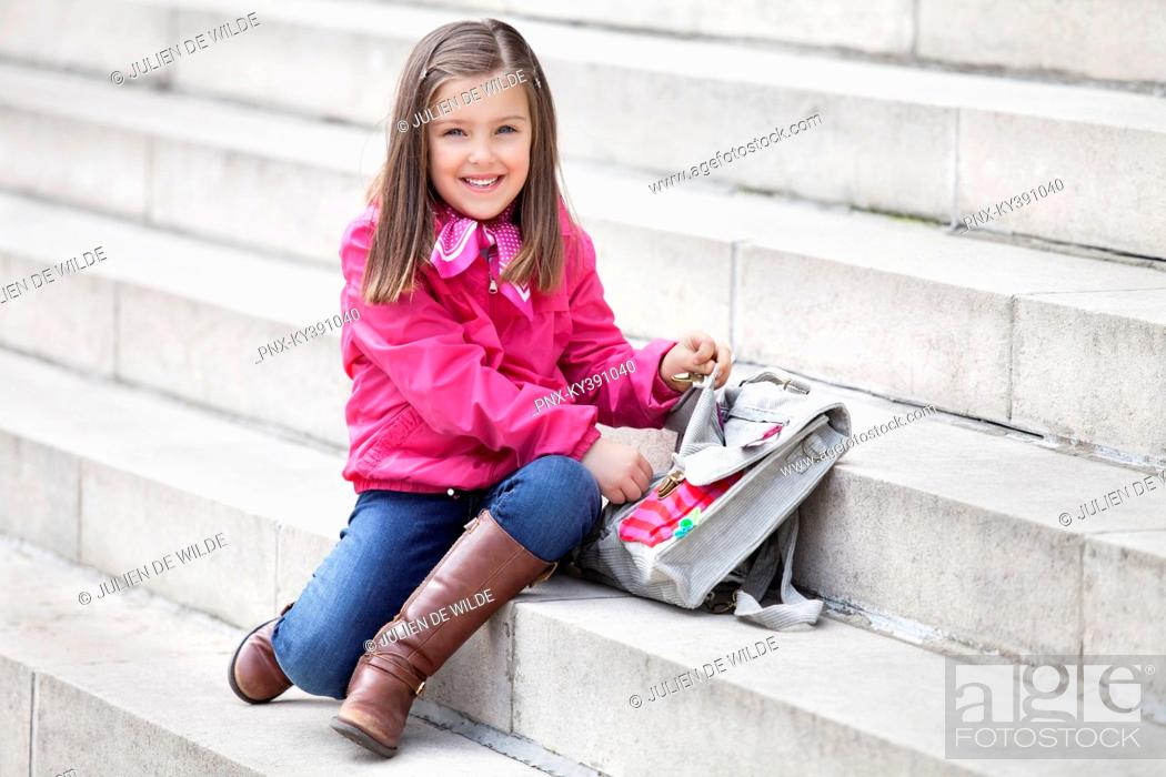Stock Photo: Portrait of a girl opening her schoolbag and smiling.