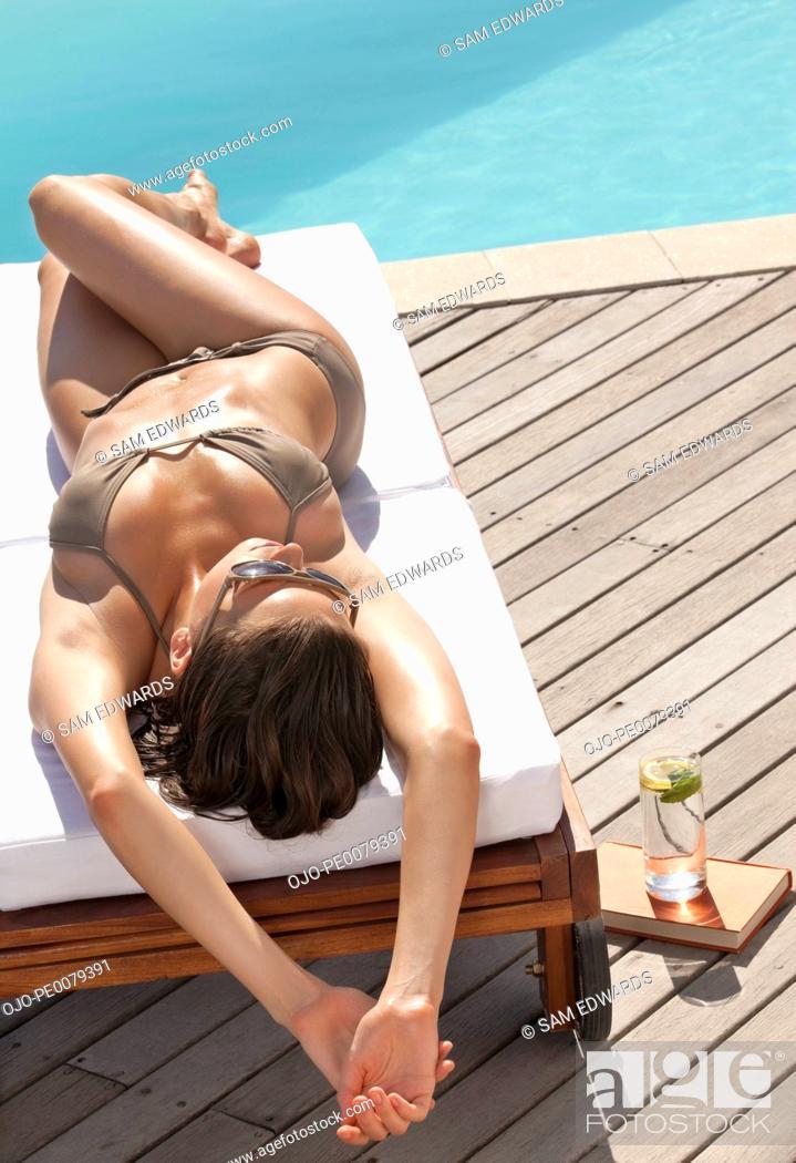 Stock Photo: Teenager sunbathing on lounge chair near swimming pool.