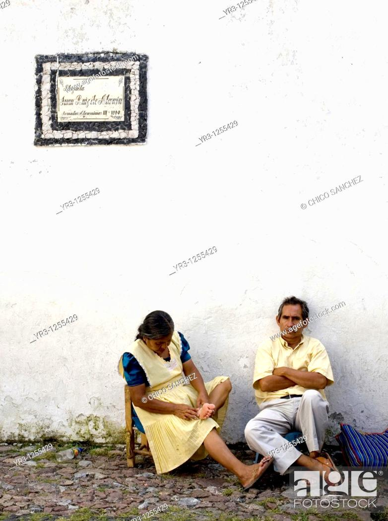 Stock Photo: A couple rest as they wait for customers at a souvenirs small market in Taxco de Alarcon, Guerrero State, Mexico.