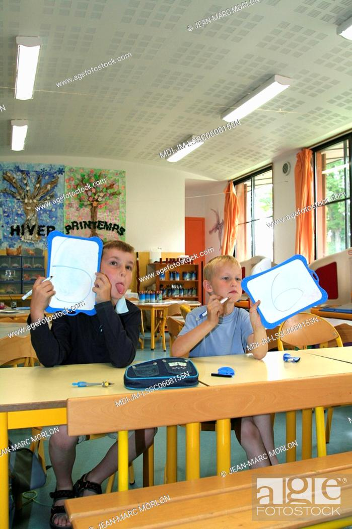 Stock Photo: Two young boys showing numbers on plastic slates, one is sticking out tongue, in a classroom.