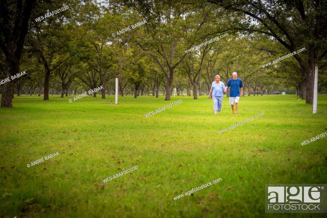 Stock Photo: USA, Texas, Senior couple walking in park.