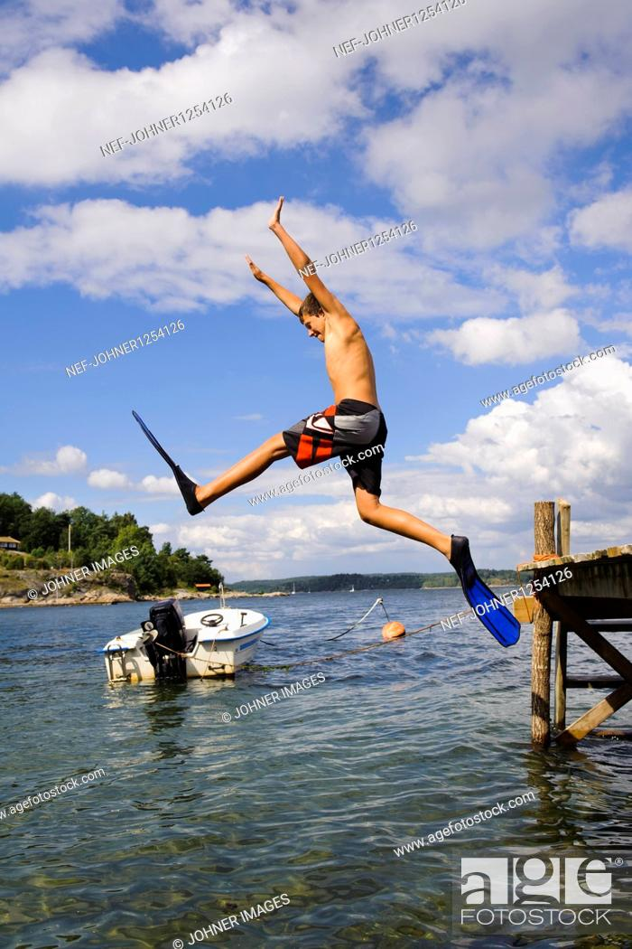 Stock Photo: A boy jumping into the water.