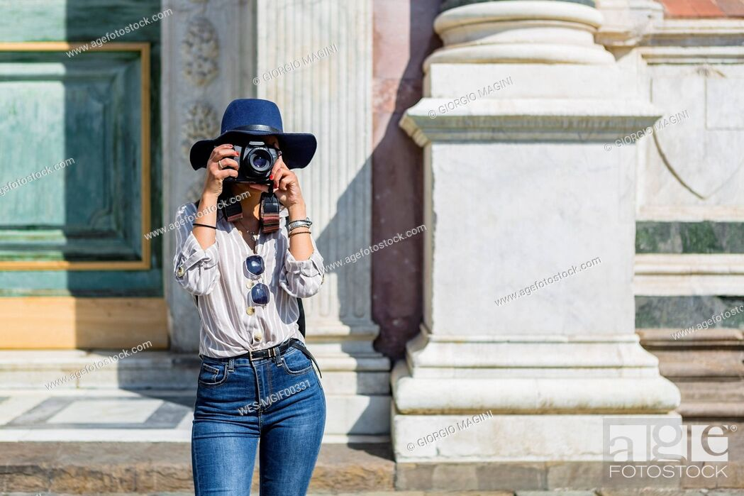 Stock Photo: Italy, Florence, young tourist taking photograph with camera.