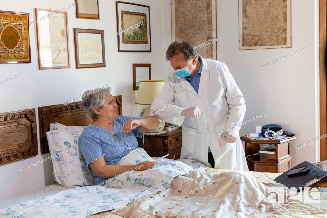 Stock Photo: A doctor in a white coat and protective face mask making a home visit to a senior woman patient, greeting by touching elbows.