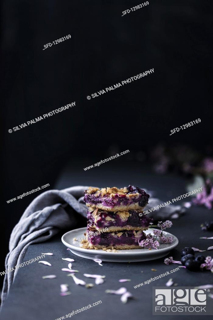 Photo de stock: Three slices of blueberry tray cake with streusel and almonds.