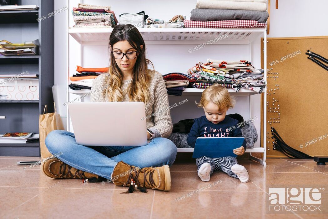 Stock Photo: Mother and little daughter sitting on the floor at home using laptop and tablet.