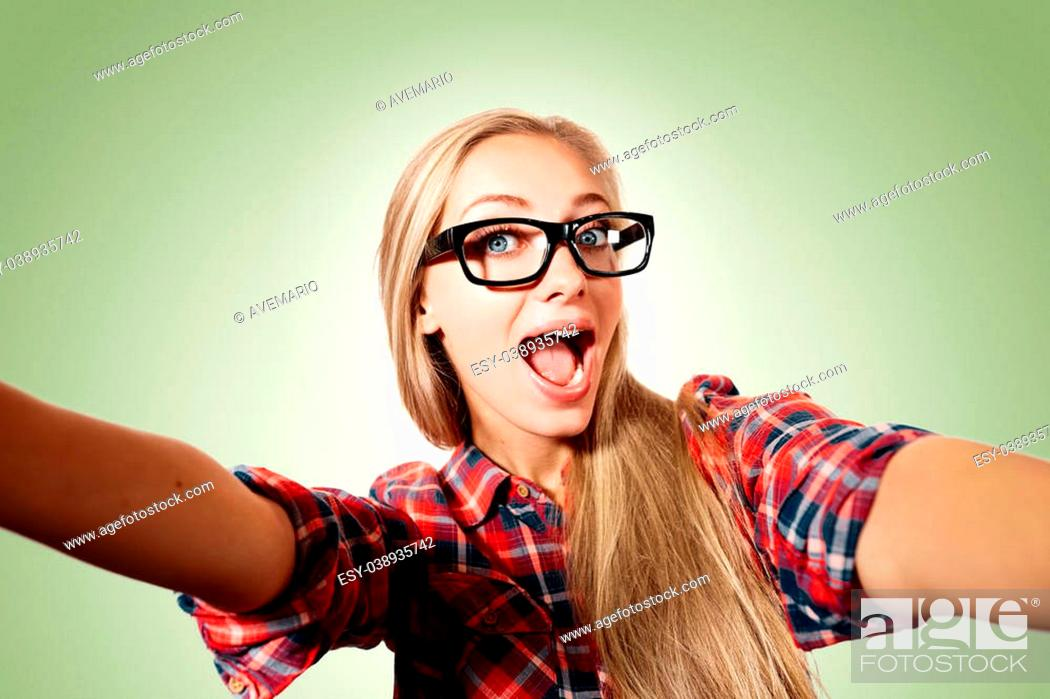 Stock Photo: Close up portrait of a young joyful blonde girl holding a smartphone digital camera with her hands and taking a selfie self portrait of herself standing against.