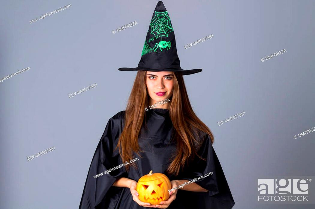 Stock Photo: Beautiful young woman in black costume of witch with black hat holding a pumpkin in her hands on blue background in studio.